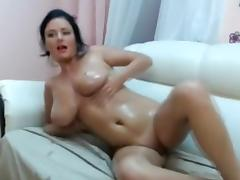 Hot stripteasing brunette on webcam seducing with her big oily boobs