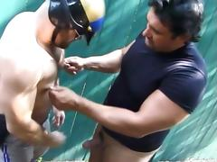 A police officer and a bad guy suck each others dicks outdoors